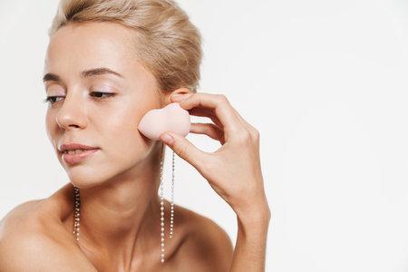 Pleased shirtless girl wearing earrings using powder sponge isolated over white background