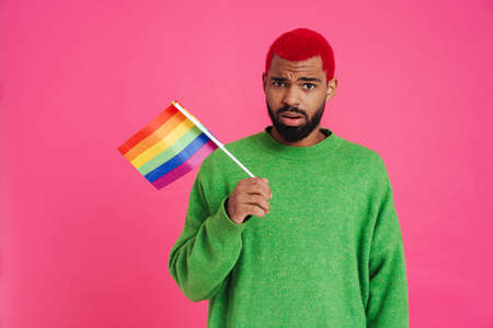 Confused african american guy posing with rainbow flag isolated over pink background