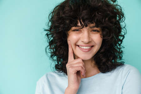 Joyful beautiful curly girl smiling and pointing finger at her cheek isolated over blue background