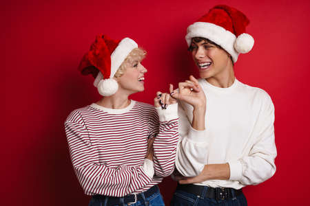 Cheerful couple in Santa Claus hats making peace gesture with pinkies together isolated over red background