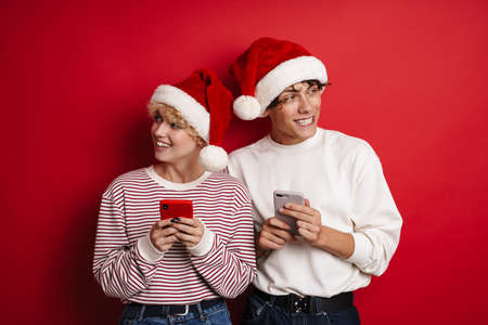 Beautiful happy couple in Santa Claus hats using smarphones isolated over red background