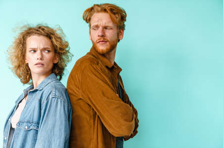 Young resentful redhead couple posing back to back isolated over blue background