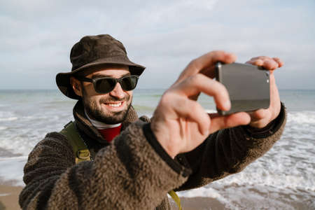 Happy unshaven man smiling while taking selfie on mobile phone at beach
