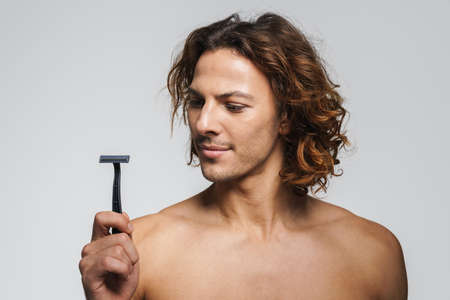 Serious shirtless handsome guy posing with razor isolated over white background