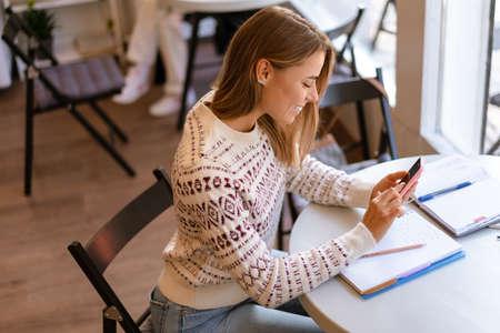 Smiling charming student girl using mobile phone while doing homework in cafe indoors Reklamní fotografie