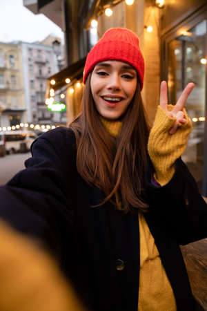Charming happy girl in hat gesturing peace sign while taking selfie photo at city street