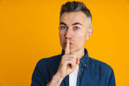 Serious handsome man showing silence gesture at camera isolated over yellow background
