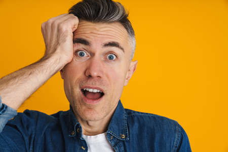 Excited handsome man expressing surprise on camera isolated over yellow background