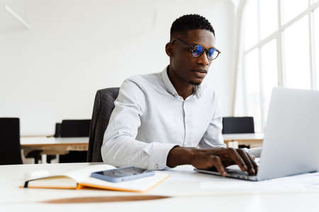 Afro american focused man in eyeglasses working with laptop while sitting in office