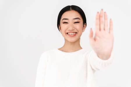 Asian cheerful nice girl smiling and showing stop gesture isolated over white background Stock Photo