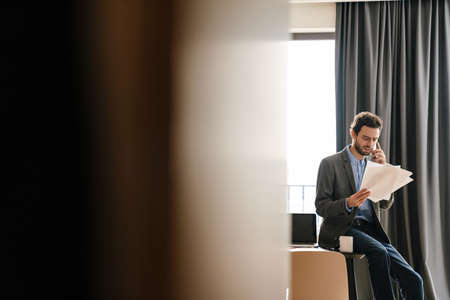 Handsome brooding businessman talking on mobile phone while examining documents indoors