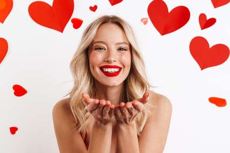 Cheerful nice girl holding copyspace and smiling isolated over white background with hearts