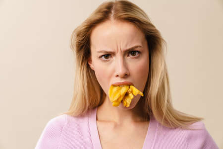 Furious beautiful girl posing with french fries in her mouth isolated over white background
