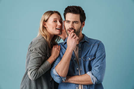 Young beautiful woman whispering secret at surprised guy isolated over blue background Reklamní fotografie