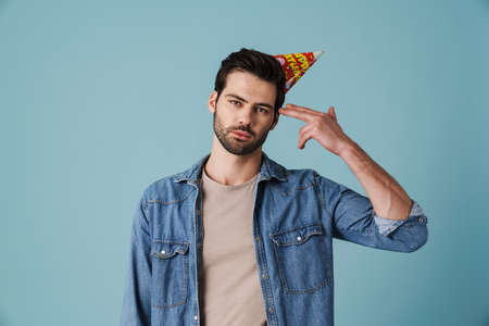 Young handsome sad man in party cone showing shot gesture isolated over blue background