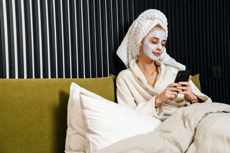 Smiling young woman wearing facial mask using mobile phone while sitting in bed, wearing bathrobe 版權商用圖片