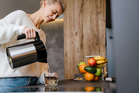 Smiling young woman making tea wihile standing in the kitchen