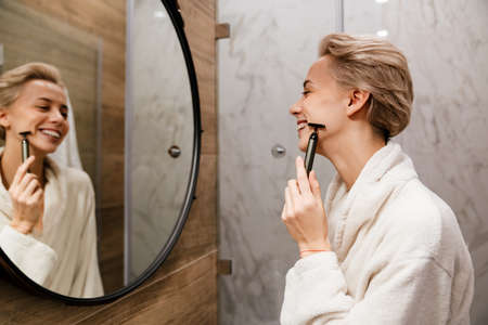 Attractive young woman doing a face massage with a cosmetic roller in bathroom in white robe