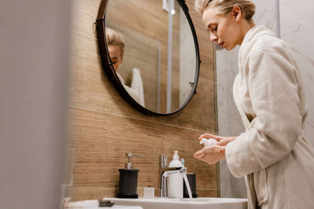 Attractive young woman applying moisturizer while standing in the bathroom