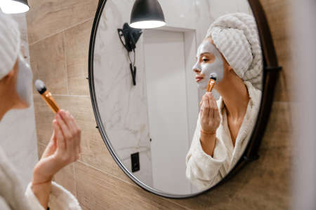 Young beautiful woman applying facial cleansing mask, looking in the mirror