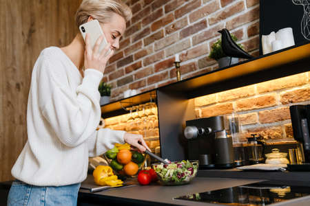 Beautiful smiling young woman using mobile phone while making healthy salad in the kitchen