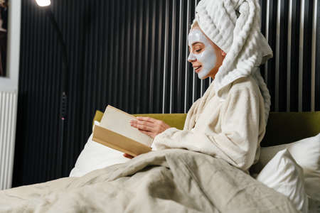 Smiling young woman wearing facial mask reading book while sitting in bed, wearing bathrobe 版權商用圖片