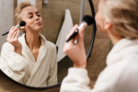 Beautiful young woman in bathrobe applying makeup with brush 版權商用圖片