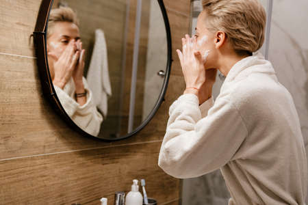 Attractive young woman applying moisturizer on her face while standing in the bathroom