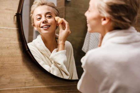 Attractive young woman wearing bathrobe applying makeup with sponge while looking in the mirror in bathroom