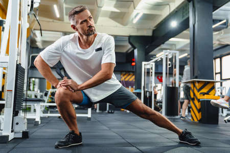 Focused grey adult sportsman stretching his legs while working out in fitness room 版權商用圖片
