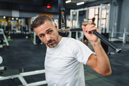 Attractive confident healthy sports man using seated lat pulldown machine in the gym