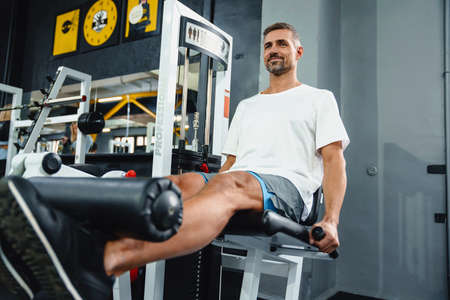 Attractive confident healthy sports man using seated leg curl machine in the gym