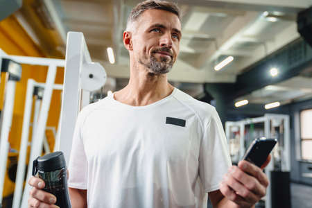 Pleased grey adult sportsman using cellphone and drinking water in fitness room