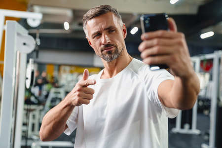 Attractive confident young man taking selfie while standing in the gym 版權商用圖片