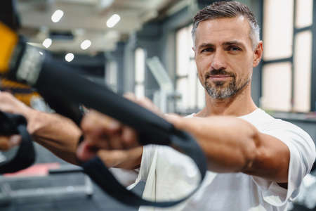 Pleased grey adult sportsman working out with exercise machine in fitness room 版權商用圖片