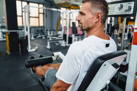 Attractive confident healthy sports man using seated leg curl machine in the gym, side view