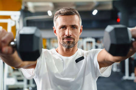 Pleased grey adult sportsman working out with dumbbells in fitness room