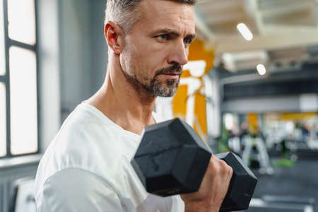 Focused grey adult sportsman working out with dumbbell in fitness room
