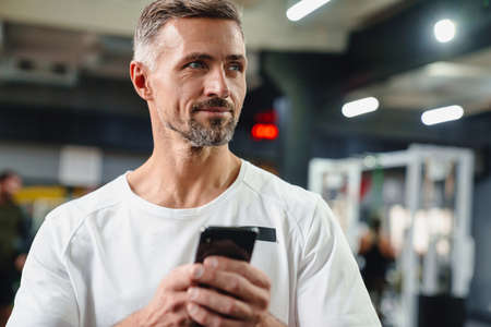 Pleased grey adult sportsman using cellphone and working out in fitness room 版權商用圖片