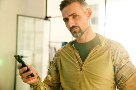 Confident masculine military man using mobile phone indoors