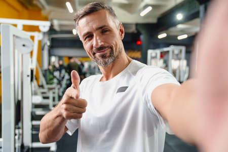 Joyful grey adult sportsman pointing finger at camera while taking selfie photo in gym