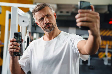 Attractive confident young man taking selfie while standing in the gym, showing water bottle 版權商用圖片
