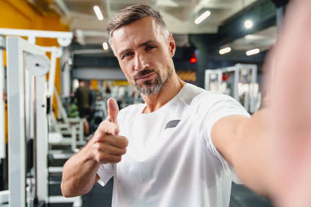 Confident grey adult sportsman pointing finger at camera while taking selfie photo in gym 版權商用圖片
