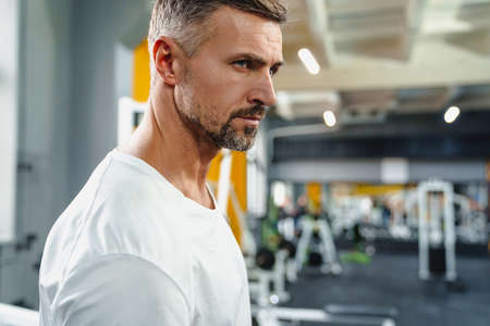 Confident grey adult sportsman working out in fitness room