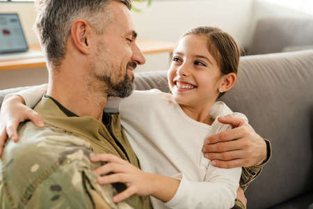 Happy masculine military man hugging his smiling daughter while sitting on sofa indoors