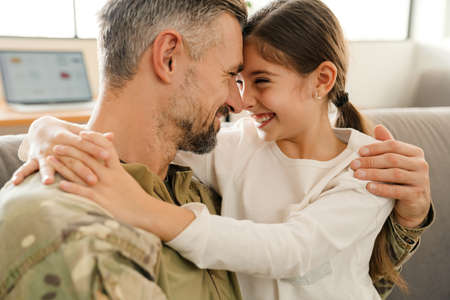 Happy military father and his daughter reunion at home. Family reunion or returning home concept 版權商用圖片