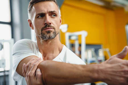 Focused grey adult sportsman stretching his arm while working out in fitness room