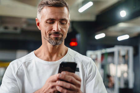 Handsome smiling young man with smartphone in gym 版權商用圖片