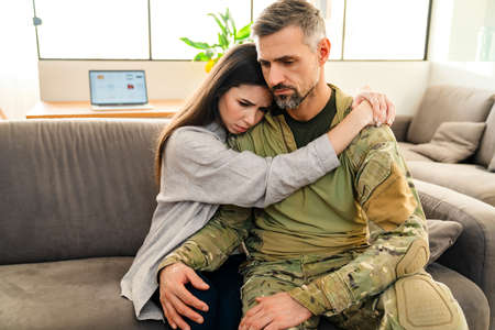 Unhappy woman hugging her military husband while sitting on sofa indoors