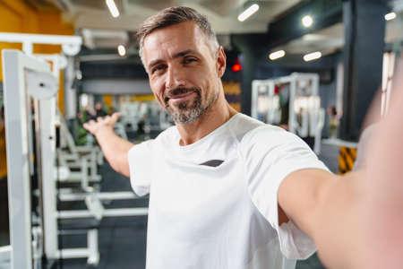 Joyful grey adult sportsman showing copyspace while taking selfie photo in gym